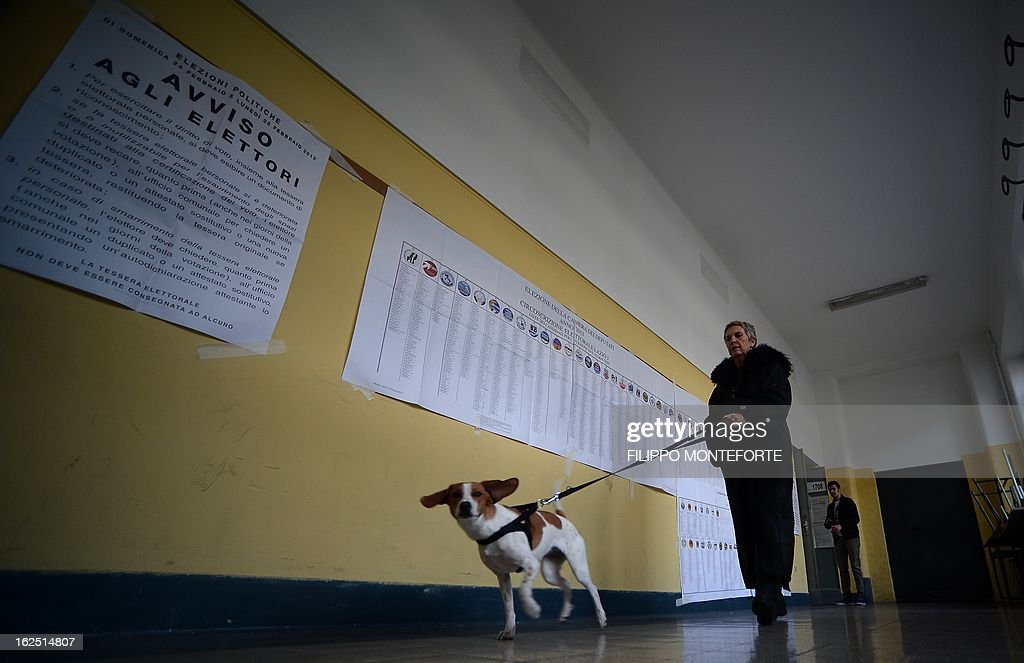 A woman walks her dog in a polling station in the center of Rome on February 24,2013 during Italy's general elections. Italians fed up with austerity voted on February 24 in the country's most important election in a generation, as Europe held its breath for signs of fresh instability in the eurozone's third economy.