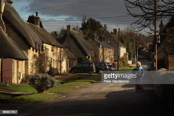 A woman walks her dog in early morning sunshine in the village of Minster Lovell in the constituency of Conservative party leader David Cameron on...