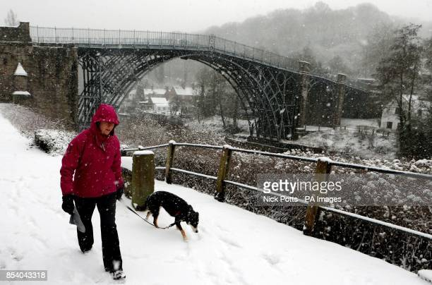 A woman walks her dog in the snow in Ironbridge Shropshire