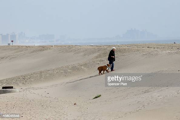 A woman walks her dog near new sand berms in the Bell Harbor neighborhood which was heavily damaged during Hurricane Sandy on October 29 2014 in New...