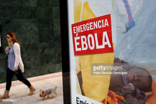 A woman walks her dog next to a bus stop banner reading 'Emergency Ebola' near the apartment building the private residence for Spanish nurse Teresa...