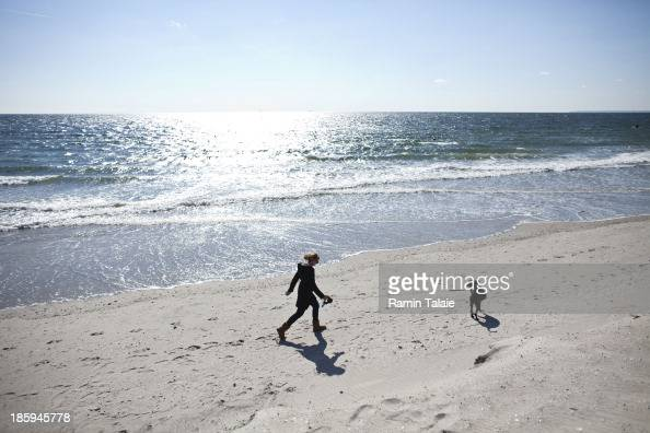 A woman walks her dog on the Rockaway Beach on October 26 2013 in the Queens borough of New York City Hurricane Sandy made landfall last year on...