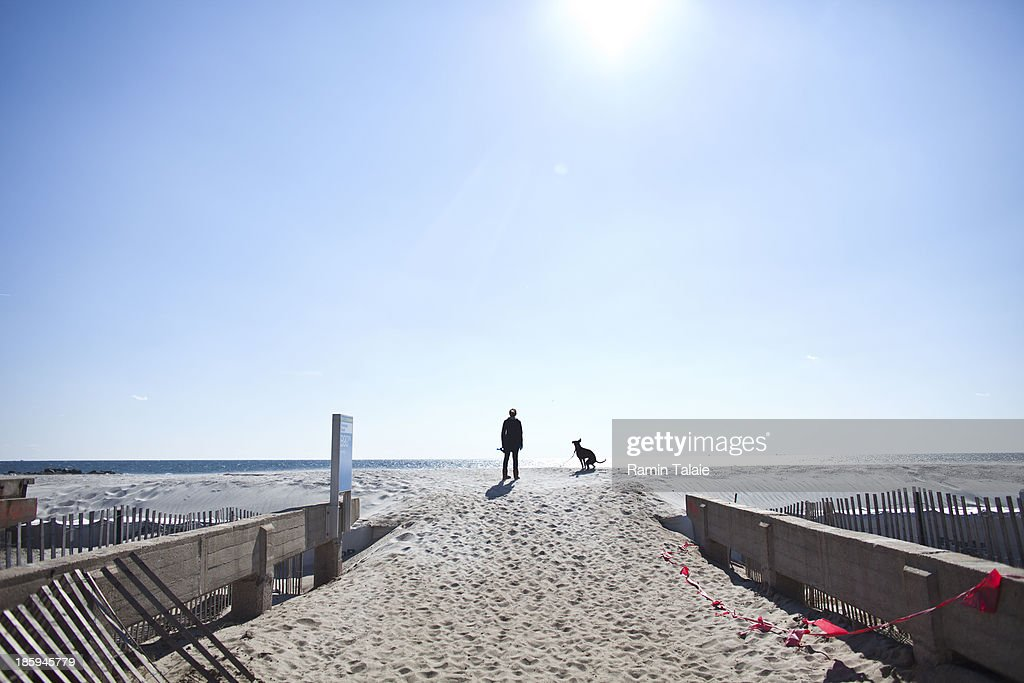 A woman walks her dog on the Rockaway Beach on October 26, 2013 in the Queens borough of New York City. Hurricane Sandy made landfall last year on October 29th near Brigantine, New Jersey and affected 24 states from Florida to Maine and cost the country an estimated $65 billion.