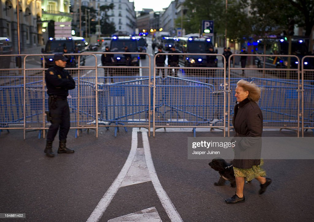 A woman walks her dog past a police barricade in front of the Spanish parliament prior to the start of a protest against spending cuts and the government of Mariano Rajoy on October 27, 2012 in Madrid, Spain. Demonstrators are protesting near the Spanish Parliament against the government's austerity measures. With the economic crisis tightening it's grip, Spain is in its second recession in three years, Rajoy's governement is presssured more and more to seek aid that can easy their debts.