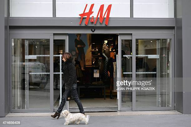 A woman walks her dog past an HM clothing store in Lyon centraleastern France on February 21 2014 AFP PHOTO / JEANPHILIPPE KSIAZEK