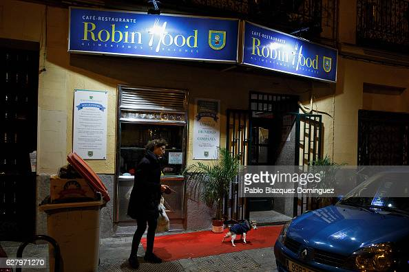 A woman walks her dog past the Robin Hood restaurant while homeless people have a free dinner inside on December 5 2016 in Madrid Spain Association...