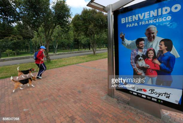 A woman walks her dogs next to a bus stop where a sign welcoming Pope Francis is displayed ahead of his upcoming visit in Bogota on August 23 2017...