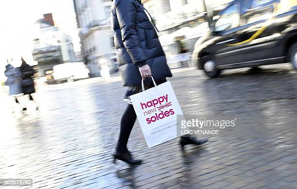 A woman walks holding a shopping bag reading 'Happy Sales' on January 6 2015 in Nantes western France on the first day of winter sales / AFP / LOIC...