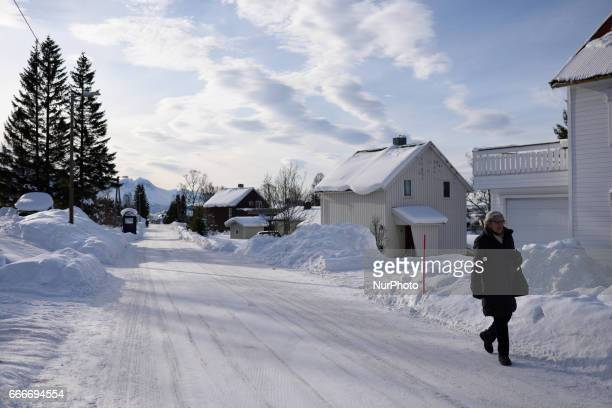 A woman walks in a a street in the snowcovered city of Tromso Northern Norway on March 08 2017 Troms is located 350 kilometres north of the Arctic...
