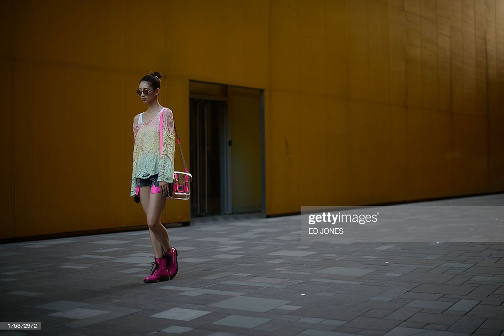 A woman walks in a popular shopping area of Beijing on August 3, 2013. China's economic planning agency on July 31 issued assurances that the year's growth goal was safe and that authorities would supply markets with ample funding. AFP PHOTO / Ed Jones