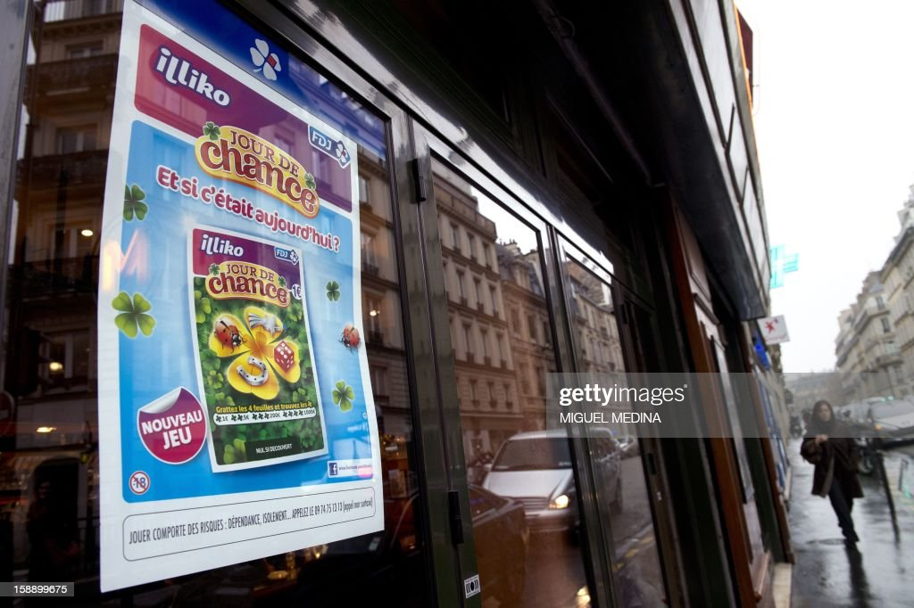 A woman walks in a street as a poster promoting a new scratchcard game called 'Jour de Chance' (Lucky day) is on display on a window, on January 3, 2013 in Paris. The Française des Jeux (FDJ), the operator of France's national lottery games, announced on January 3, 2013 that its revenue increased by 6,1% to reach 12,1 billion of euros in 2012. AFP PHOTO/MIGUEL MEDINA