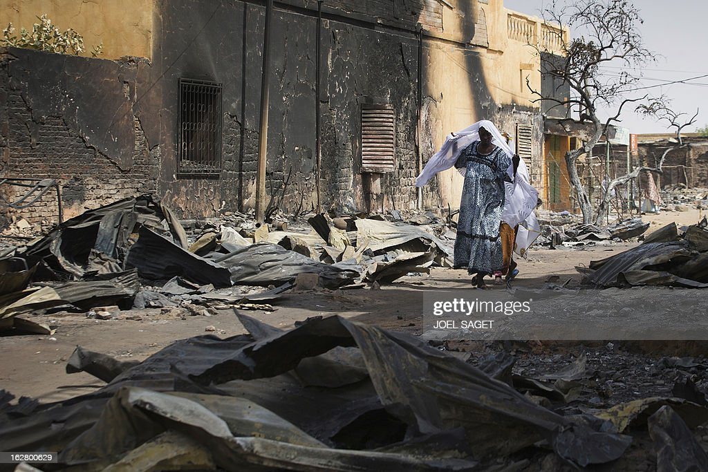A woman walks in a street destroyed after an attack on February 27, 2013 in Gao. Chad's President Idriss Deby Itno on Wednesday urged the Malian army and West African force to speed up the deployment of troops to northern Mali to help fight Al-Qaeda-linked rebels. AFP PHOTO /JOEL SAGET