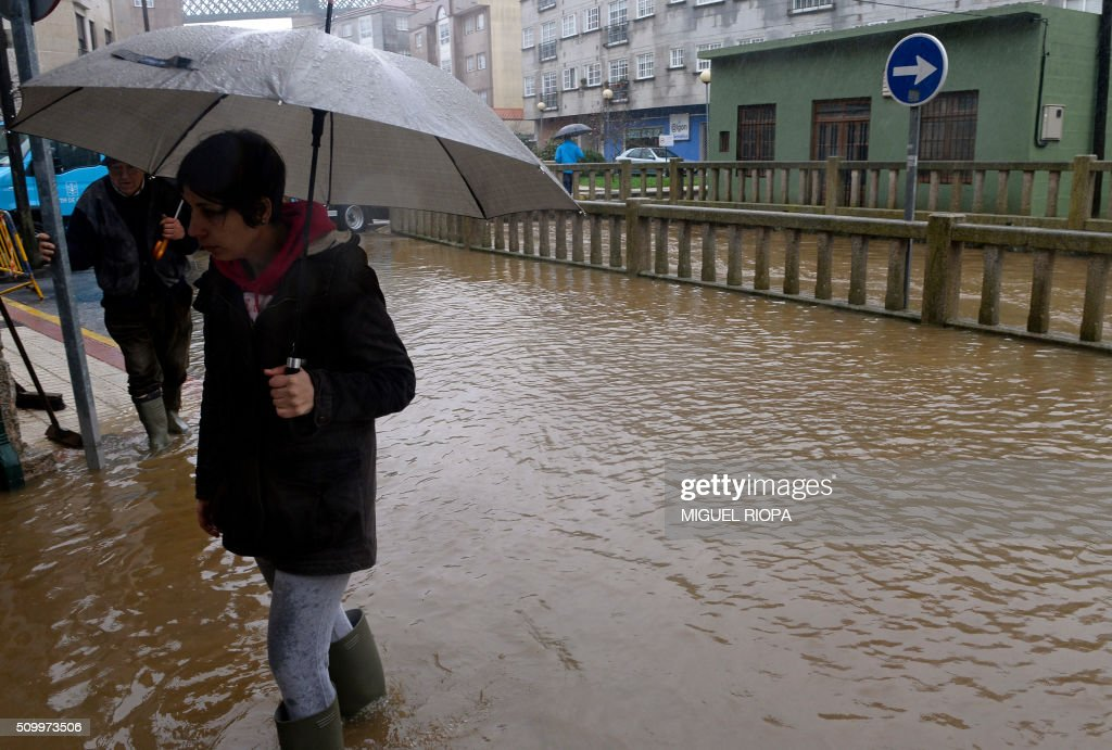 A woman walks in flooded area next to the river Tea in Ponteareas, northwestern Spain, on February 13, 2016. / AFP / AFP or licensors / MIGUEL RIOPA