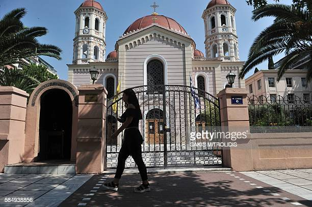 A woman walks in font of the cathedral of Thessaloniki on 1 August 2016 A Greek court on August 1 released 26 anarchists who had disrupted a Sunday...