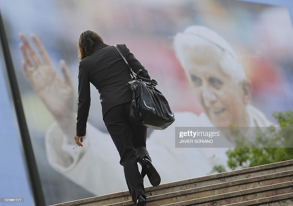 A woman walks in front of a big placard of Pope Benedict XVI in Lisbon, on May 10, 2010, on the eve of Pope Benedict XVI's official visit to Portugal, on May 11-14.