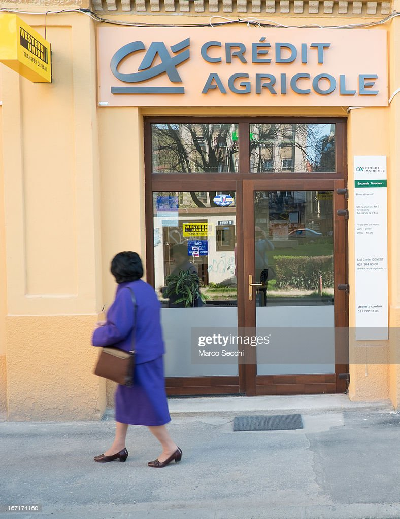 A woman walks in front of a branch of Credit Agricole on April 16, 2013 in Timisoara, Romania. Romania has abandoned a target deadline of 2015 to switch to the single European currency and will now submit to the European Commission a programme on progress towards the adoption of the Euro, which for the first time will not have a target date.