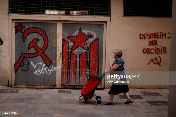 A woman walks in front of a graffiti reading in Catalan 'We disobeyed to decide' in Mataro a town near Barcelona on September 8 2017 Spain's top...