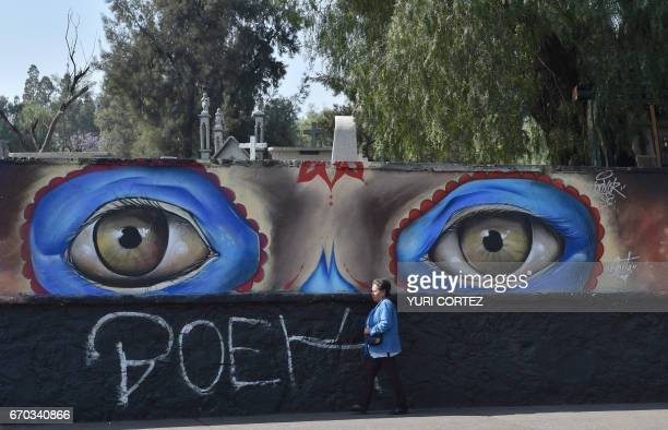 A woman walks in front of a mural painted on a wall of the municipal cemetery of the Iztapalapa delegation in the southeast of Mexico City on April...