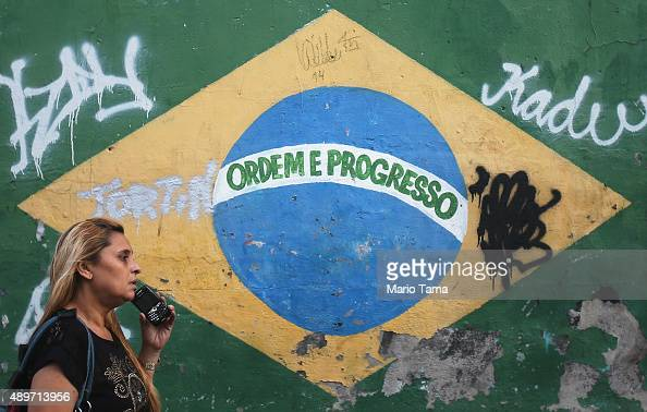 A woman walks in front of a painted Brazilian flag and other graffiti on a downtown street on September 23 2015 in Rio de Janeiro Brazil The US...