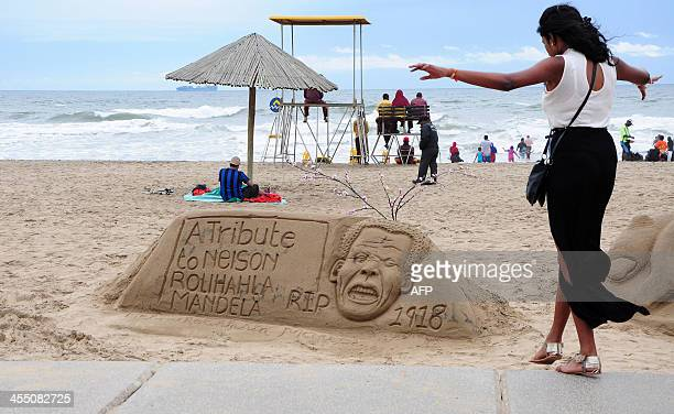 A woman walks in front of a sand sculpture in tribute to late former South African President Nelson Mandela on Durban's beach on December 11 2013...