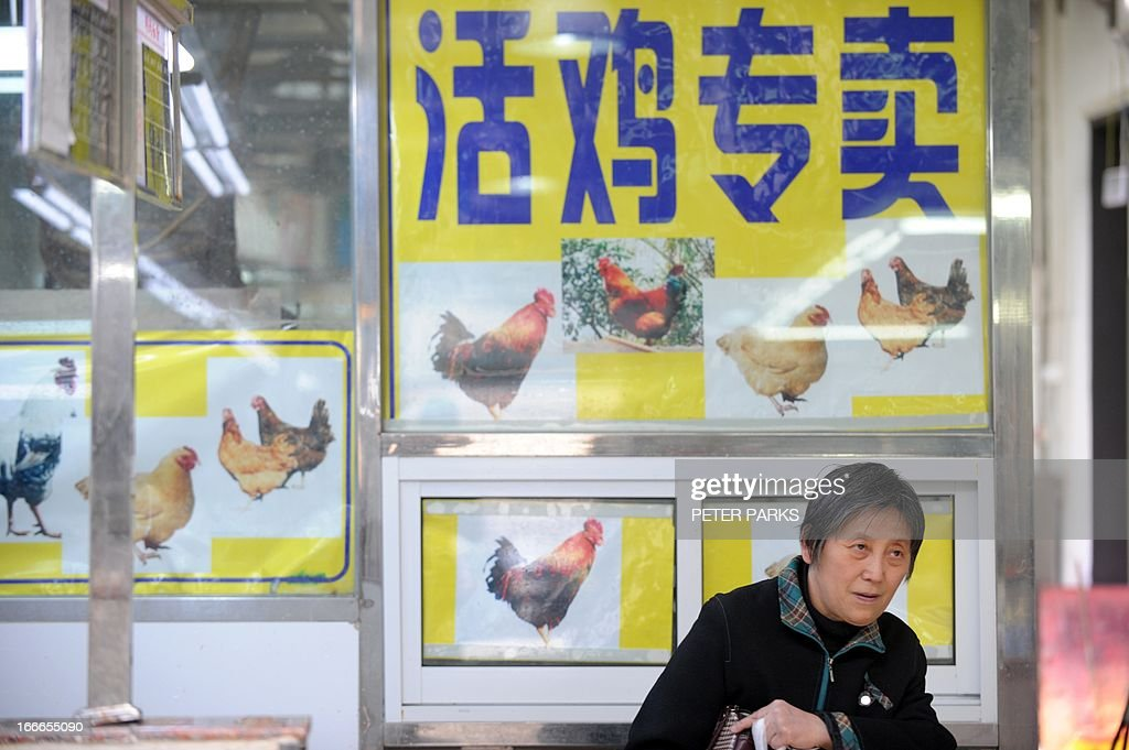 A woman walks in front of a stall which used keep live chickens for sale which is now closed to control bird flu in a wet market in Shanghai on April 15, 2013. China's poultry industry lost 1.6 billion USD (10 billion yuan) in the week after the H7N9 bird flu virus began infecting humans, state-run media said as they sought to discourage panic with 60 people confirmed as infected and 13 who have died in the two weeks since Chinese authorities said they found the strain in humans for the first time. AFP PHOTO/Peter PARKS