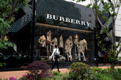 A woman walks in front of Burberry's new flagship store on April 25 2014 in Shanghai China