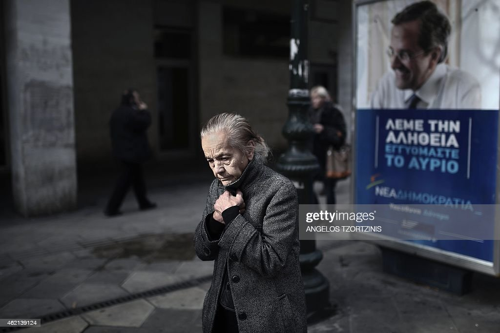 A woman walks in front of campaign posters of Greek Prime Minister <a gi-track='captionPersonalityLinkClicked' href=/galleries/search?phrase=Antonis+Samaras&family=editorial&specificpeople=970799 ng-click='$event.stopPropagation()'>Antonis Samaras</a> in Athens, as the nation goes to the polls, on January 25, 2015. Greece votes today in a crucial general election that could bring the anti-austerity Syriza party to power and lead to a re-negotiation of the country's international bailout.