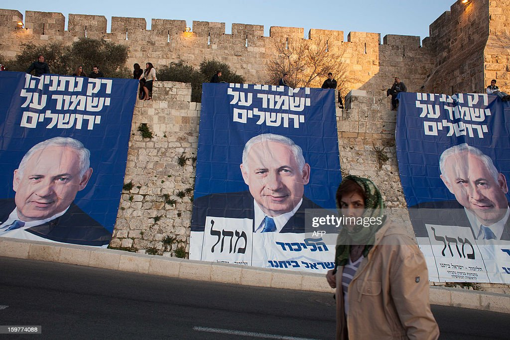A woman walks in front of campaign posters of Israeli Prime Minister and Likud party leader Benjamin Netanyahu, with text reading in Hebrew: ' Only Netanyahu will guard Jerusalem' along the walls of the old city of Jerusalem on January 20, 2013, ahead of the Israeli general election on January 22. == ISRAEL
