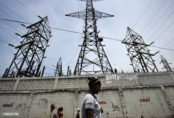 A woman walks in front of electricity pylons in Caracas Venezuela on April 10 2011 The fragility of the Venezuelan power system may reissue this year...