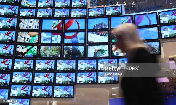 A woman walks in front of LCD television monitors at the Samsung stand ahead of the opening evening at the IFA consumer elctronics trade fair on...