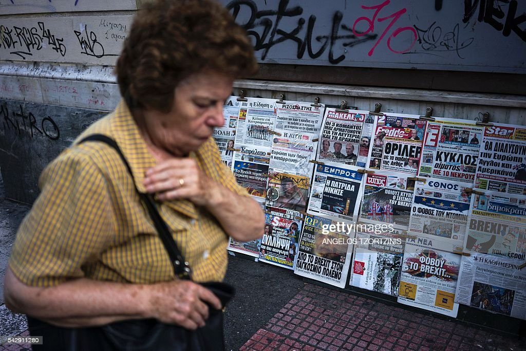 A woman walks in front of newspapers with some headlines reporting the result of the UK's vote to leave the EU in the June 23 referendum, in Athens on June 25, 2016. The pound plunged and world stock markets slumped on June 24, 2016 after Britain's shock vote to leave the European Union, fuelling a wave of global uncertainty. Sterling crashed 10 percent to a 31-year low at one point and the euro also plummeted against the dollar, as the Brexit result caught markets by surprise. / AFP / Angelos Tzortzinis
