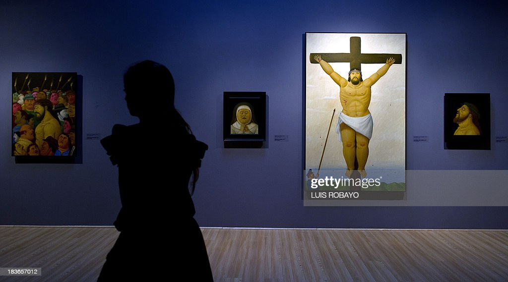 A woman walks in front of paintings of the exhibition 'Via Crucis, the passion of Christ' of Colombian artist Fernando Botero, on October 8, 2013, in Cali, department of Valle del Cauca, Colombia. Botero was the curator of his own exhibition, which is composed of 27 oil paintings and 34 drawings combining traditional aspects of Catholicism and the modern world. AFP PHOTO / LUIS ROBAYO