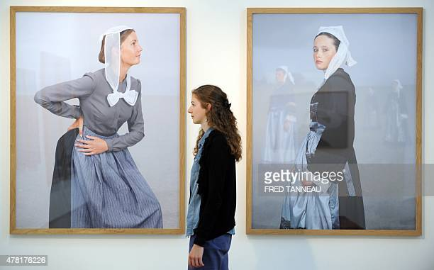 A woman walks in front of pictures by French photographer Charles Freger during an exhibition on traditional costumes and headdresses in Brittany on...