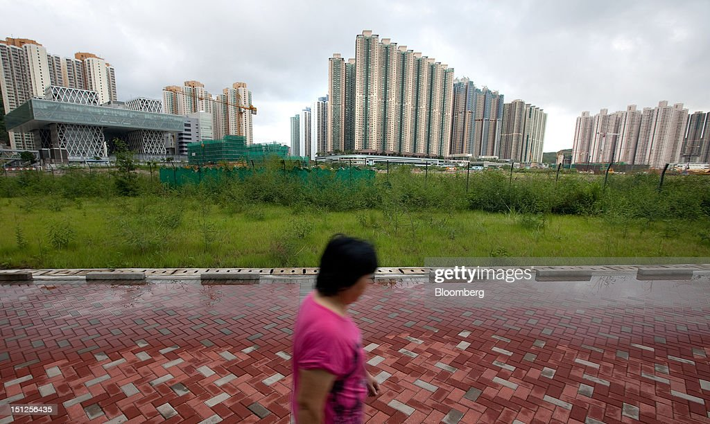A woman walks in front of residential tower blocks in the Tseung Kwan O area of the New Territories in Hong Kong, China, on Tuesday, Sept. 4, 2012. Hong Kong will boost the supply of homes and give preference to local buyers as it seeks to cool housing prices that have surged to the world's most expensive, fueled by record-low interest rates and Chinese investment. Photographer: Daniel J. Groshong/Bloomberg via Getty Images