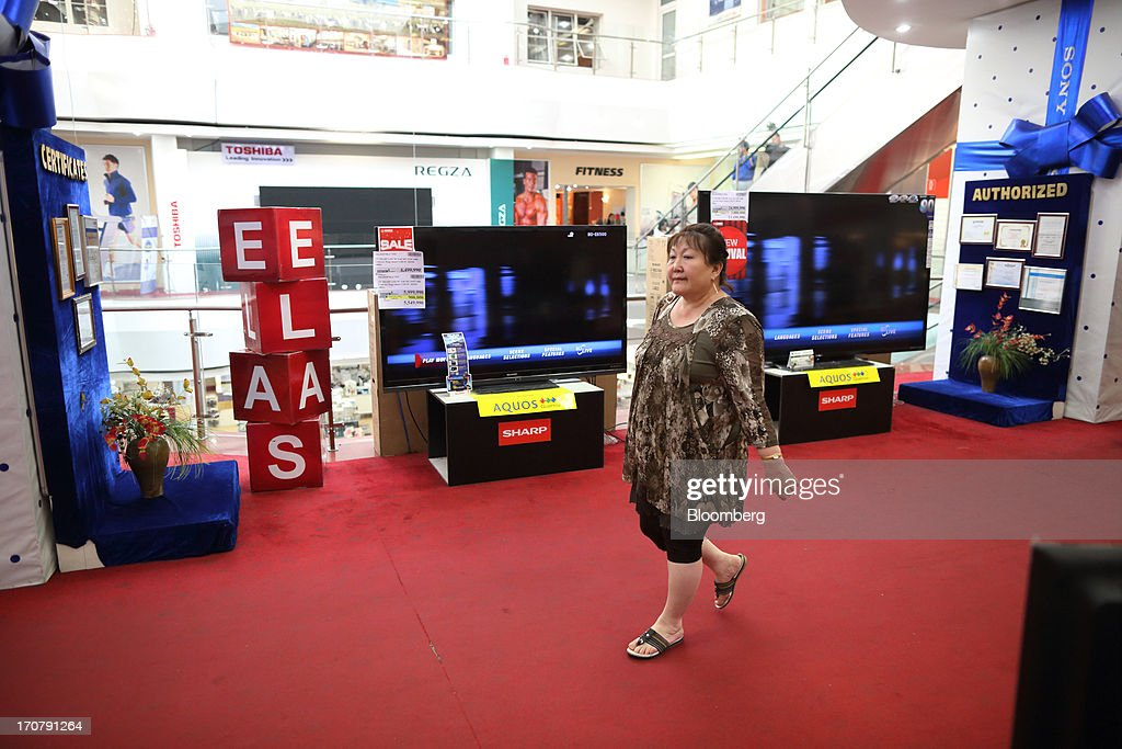 A woman walks in front of Sharp Corp. televisions at a department store in Ulaanbaatar, Mongolia, on Wednesday, June 12, 2013. Mongolia, a country of almost 2.9 million people, is experiencing double-digit growth and new opportunities in the mining industry. Photographer: Tomohiro Ohsumi/Bloomberg via Getty Images