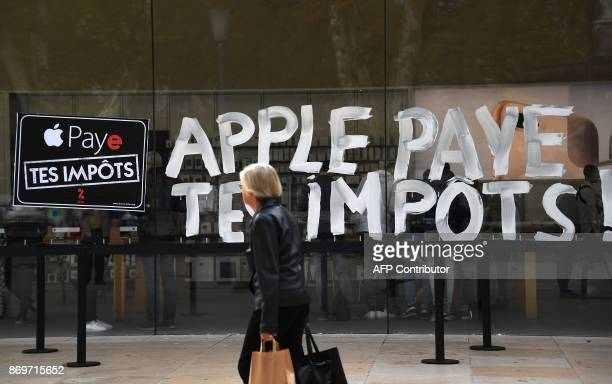 A woman walks in front of the Apple Store bearing signs reading 'Apple pay your taxes' during a protest of activists of the Association for the...