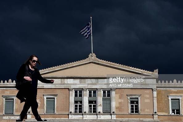 A woman walks in front of the Greek Parliament in Athens on April 7 2015 Greek lawmakers voted on April 7 to set up a committee to examine the...