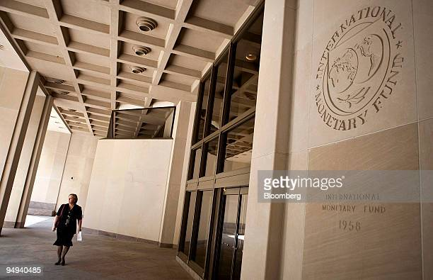 A woman walks in front of the International Monetary Fund building in Washington DC US on Friday April 24 2009 The IMF and World Bank's Global...