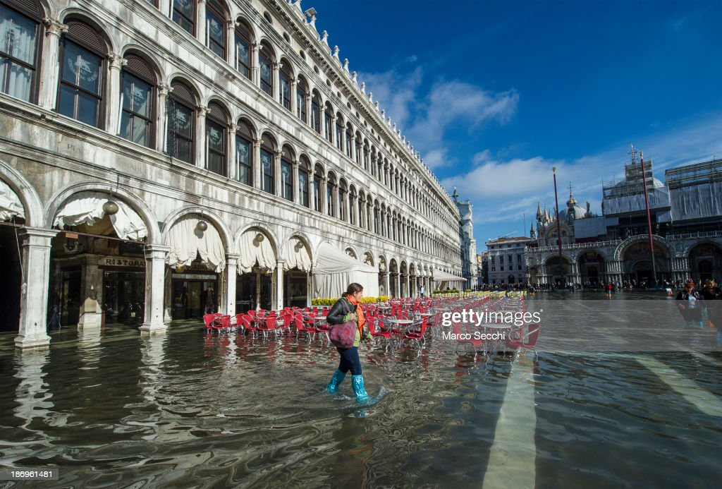 A woman walks in Saint Mark's Square during today's Acqua Alta on November 5, 2013 in Venice, Italy. The high tide, or acqua alta as it is locally known, is a natural event most commonly affecting the city during Autumn and Winter.