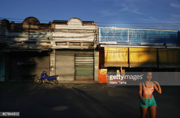 A woman walks in the Caju neighbourhood which houses two forlorn shipyards along Guanabara Bay on August 8 2017 in Rio de Janeiro Brazil The once...