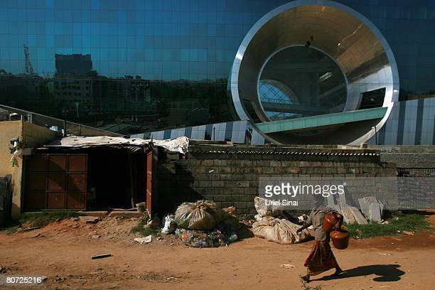 A woman walks in the slums surrounding the Electronic city on April 13 2008 in Bangalore India Many residents work for multinational cooperations and...