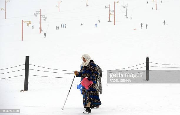 A woman walks in the snow at the Oukaimeden ski resort in the Atlas Mountains 30 kilometres from the popular tourist resort of Marrakesh on February...