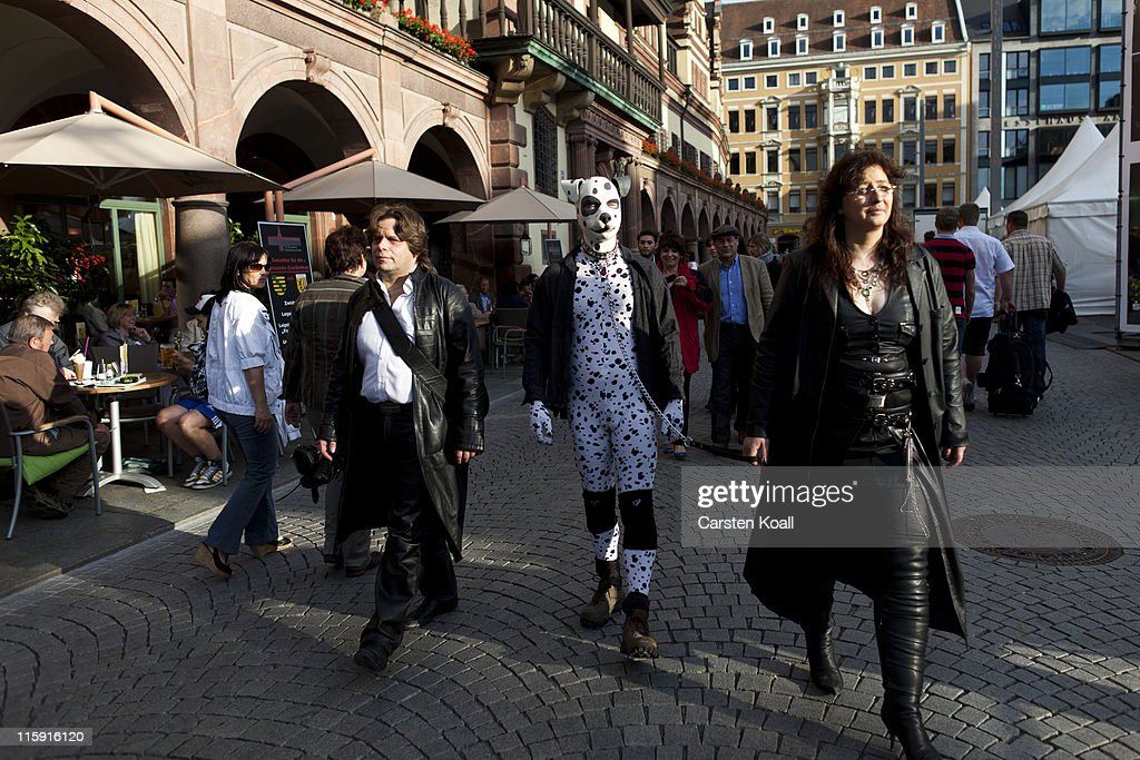 A woman walks in the streets with a man dressed as a dalmatian during the annual Wave Gotik music festival on June 11, 2011 in Leipzig, Germany. The festival began in the 1990s and has since grown into one of the biggest gatherings of Goth scene followers in Europe with around 20,000 participants. Many of those attending wear elaborate outfits and make-up for which they require hours of painstaking preparation and that also show a departure from the traditional black of the Goth scene. Punk remains a strong influence in today's Goth style as witnessed in Leipzig, but newer trends, with names like Cybergoth and Steampunk, have emerged that blend bold colors, Victorian fashion elegance and 19th and 20th century factory accessories into a look reminiscent of a mutated Venetian carnival. The five-day festival includes performances by around 200 bands.