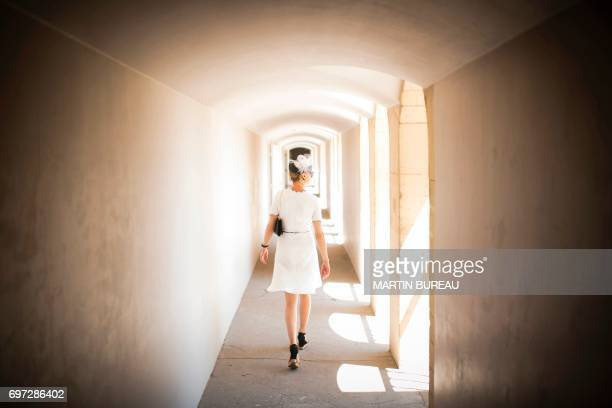 TOPSHOT A woman walks in the tribune prior to the start of the Prix de Diane a 2100meters flat horse race on June 18 2017 at the Chantilly hippodrome...