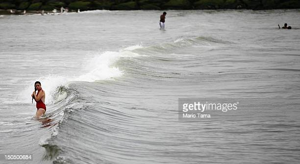 A woman walks in the waves at Rockaway Beach on August 19 2012 in the Queens borough of New York City Over the last few years the Rockaways peninsula...