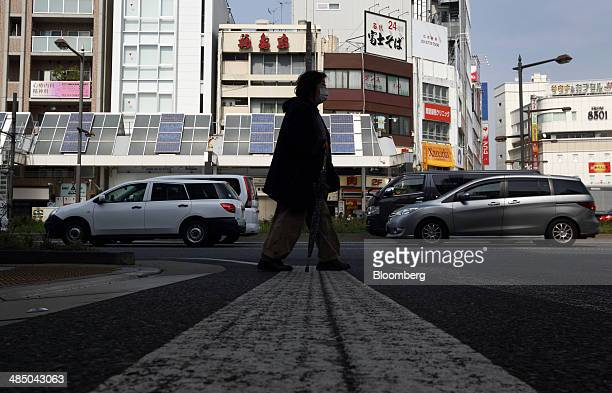 A woman walks in Tokyo Japan on Wednesday April 16 2014 Japan's population slid for a third year with the proportion of people over the age of 65 at...