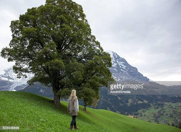 を歩く女性、山メドウ