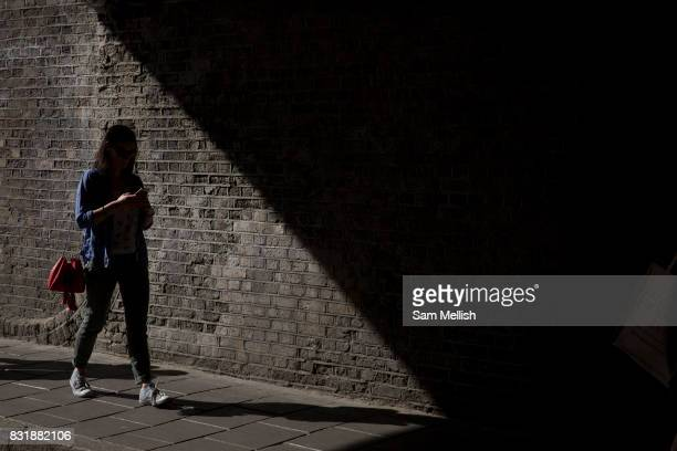 A woman walks into the shadows of London Fields arches while looking at her mobile phone on 27th May 2017 in London United Kingdom London Fields is a...