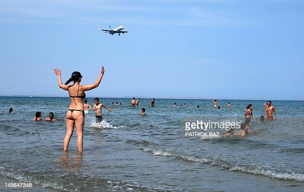 A woman walks into the water at McKenzie beach as a charter plane carrying tourists approaches Larnaca airport on the southern coast of the east...