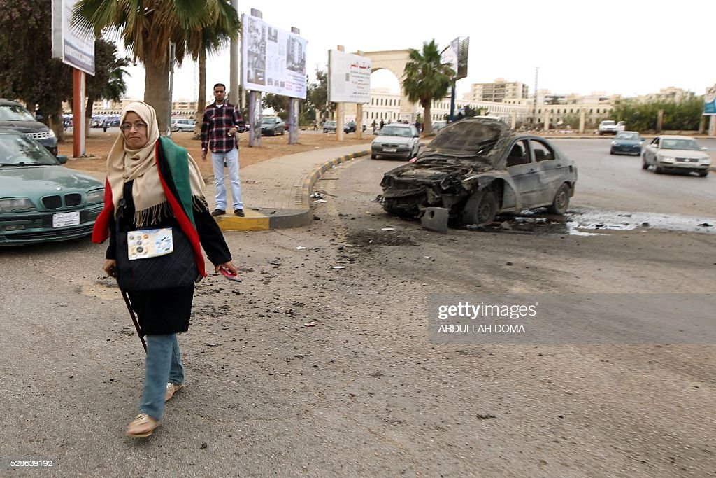 A woman walks near a damaged car after shelling hit a demonstration in the eastern coastal city of Benghazi calling for military forces to re-capture the southern city of Sirte from the Islamic State (IS) group without foreign intervention on May 6, 2016. The head of Libya's unity government announced plans the previous month for a concerted campaign to drive the Islamic State group out of the North African country, but without foreign intervention. The unity government fears that separate operations in Sirte could spark clashes between the multitude of different fighting forces in Libya and play into the jihadists' hands. DOMA